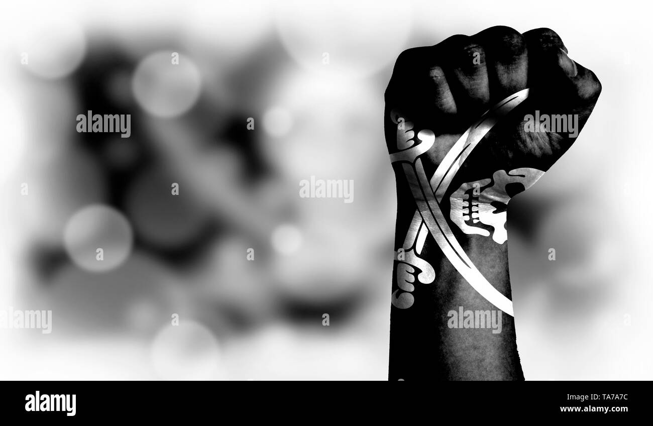 Flag of Pirates black painted on male fist, strength,power,concept of conflict. On a blurred background with a good place for your text. - Stock Image