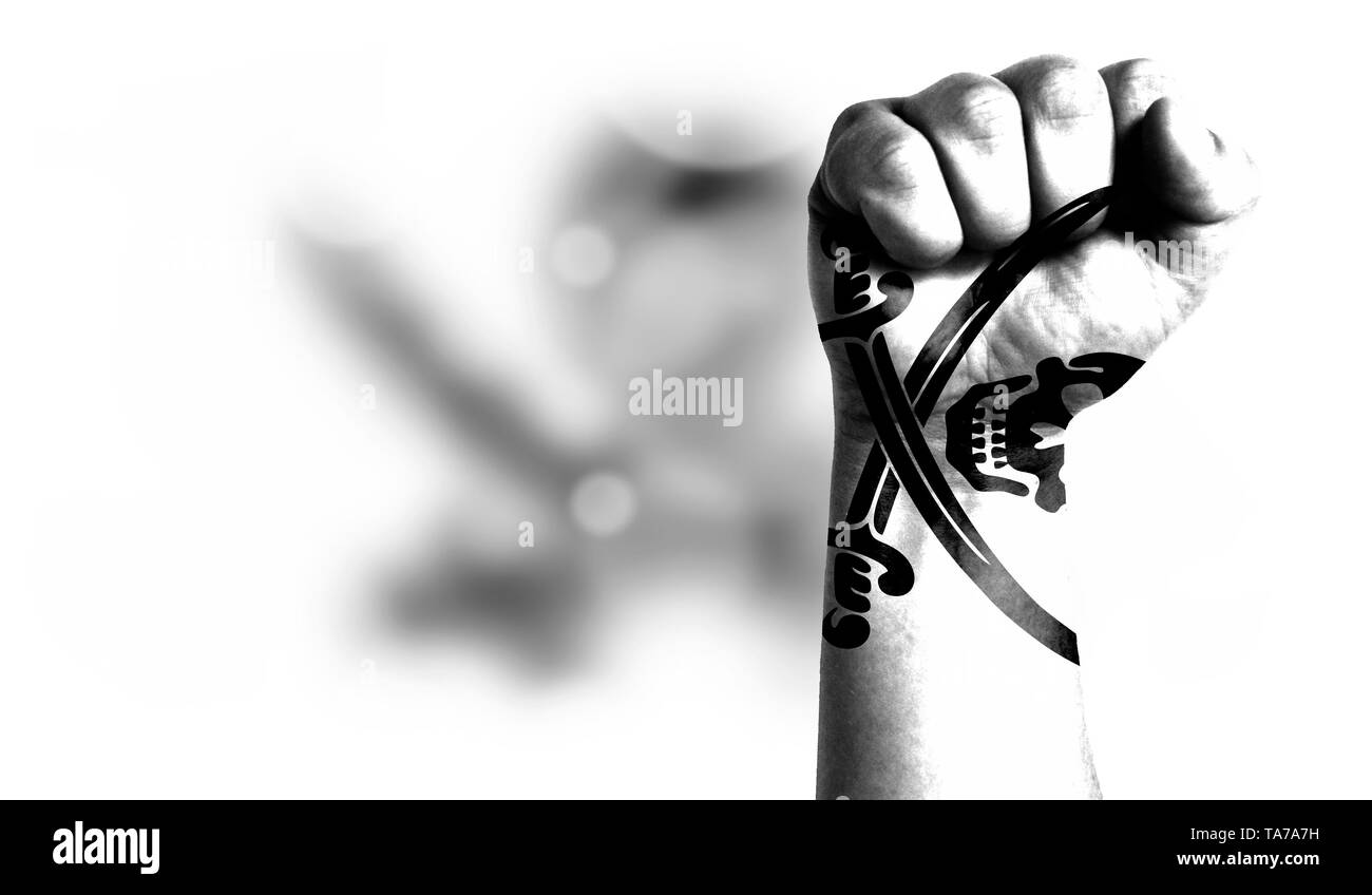 Flag of Pirates white painted on male fist, strength,power,concept of conflict. On a blurred background with a good place for your text. - Stock Image