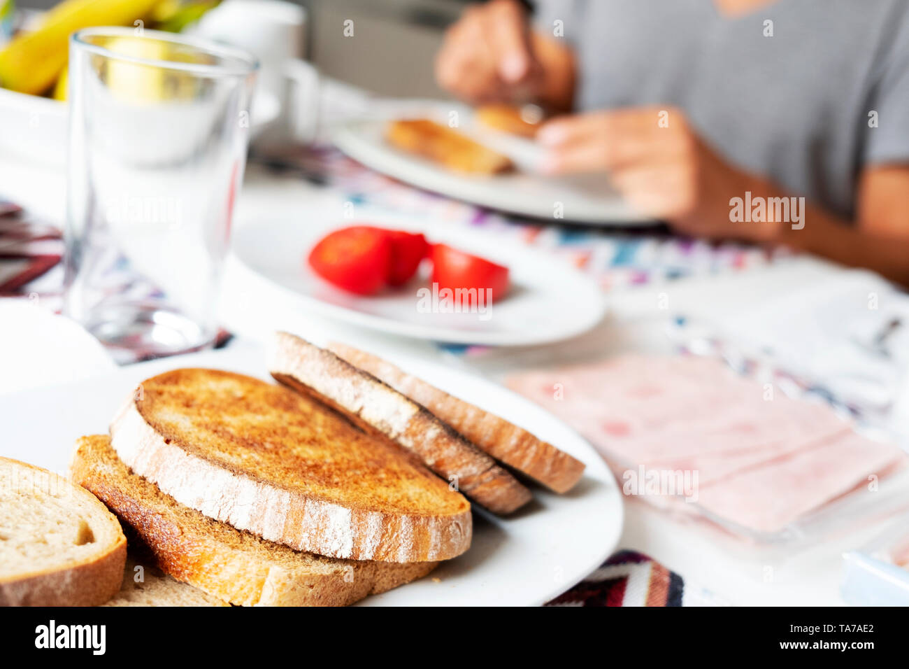 closeup of some toasts in a plate on a table set for breakfast, while a man, sitting at the table and wearing a casual gray T-shirt, spreads some jam  - Stock Image