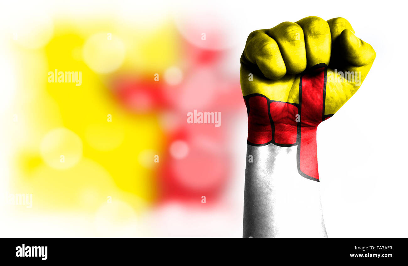 Flag of Nunavut painted on male fist, strength,power,concept of conflict. On a blurred background with a good place for your text. - Stock Image