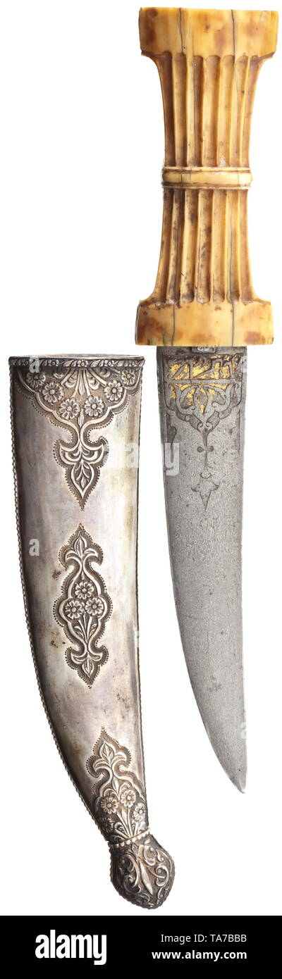 A chiselled Ottoman khanjar, 17th century Double-edged wootz-Damascus steel blade with traces of gold plating and chiselled on both sides of the root with ornaments and calligraphic cartouches. Robust, fluted walrus ivory grip of lenticular cross-section. Silver scabbard from the 18th century decorated with a frieze of raised decorative rivets with finely struck floral cartouches with a different design on either side. Length 32 cm. Typical dagger from the time of the Turkish Wars with a scabbard of slightly later date. historic, historical, Otto, Additional-Rights-Clearance-Info-Not-Available Stock Photo