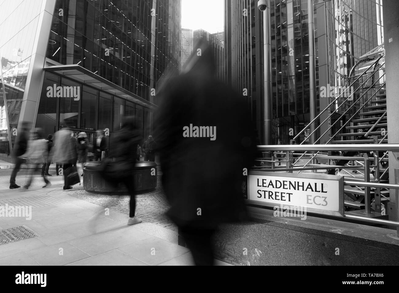 Black and white image of city buildings and people, with motion blur, Leadenhall Street, City of London. - Stock Image