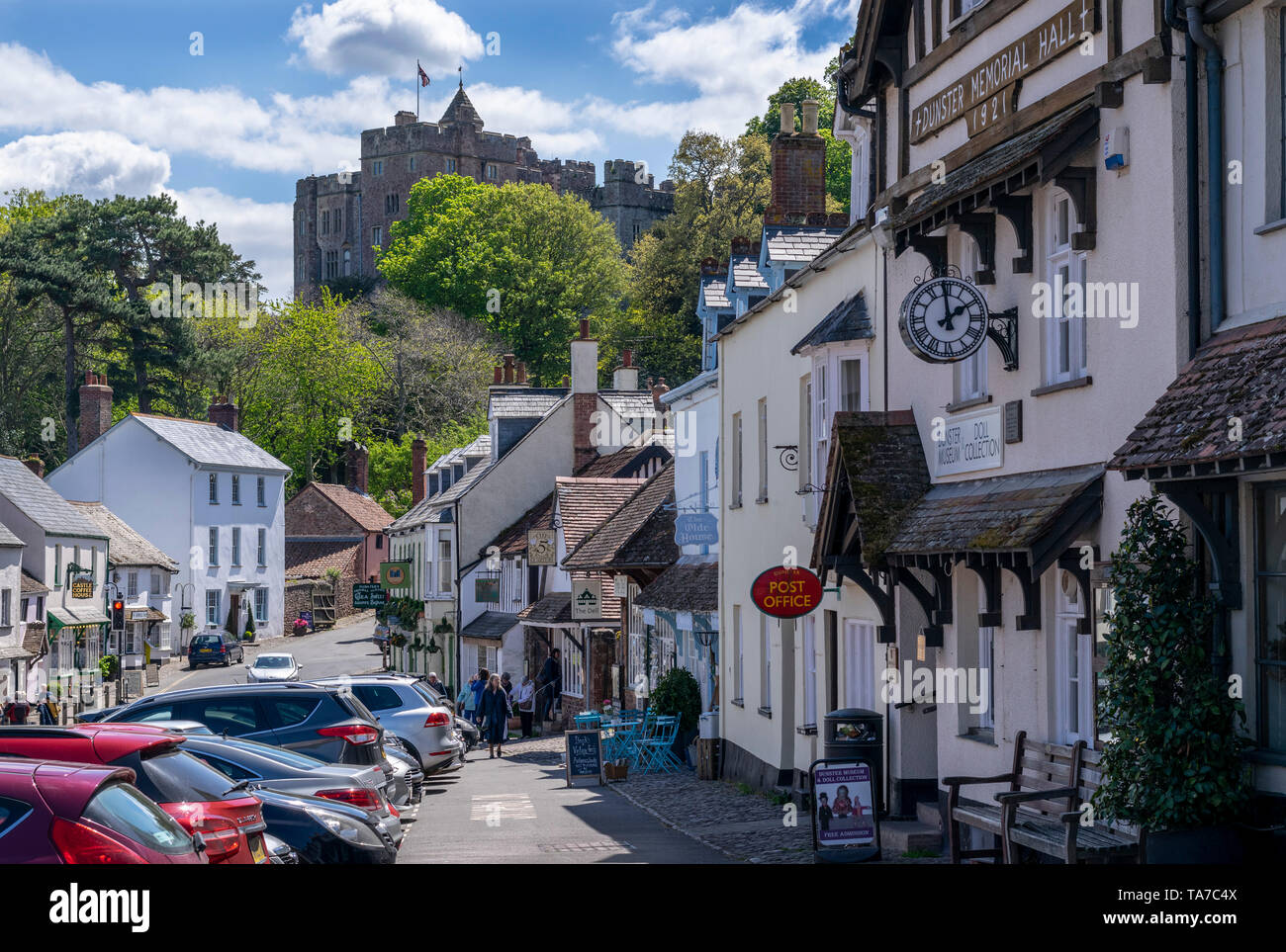Dunster Village in Somerset, England UK with Dunster Castle in the background - Stock Image