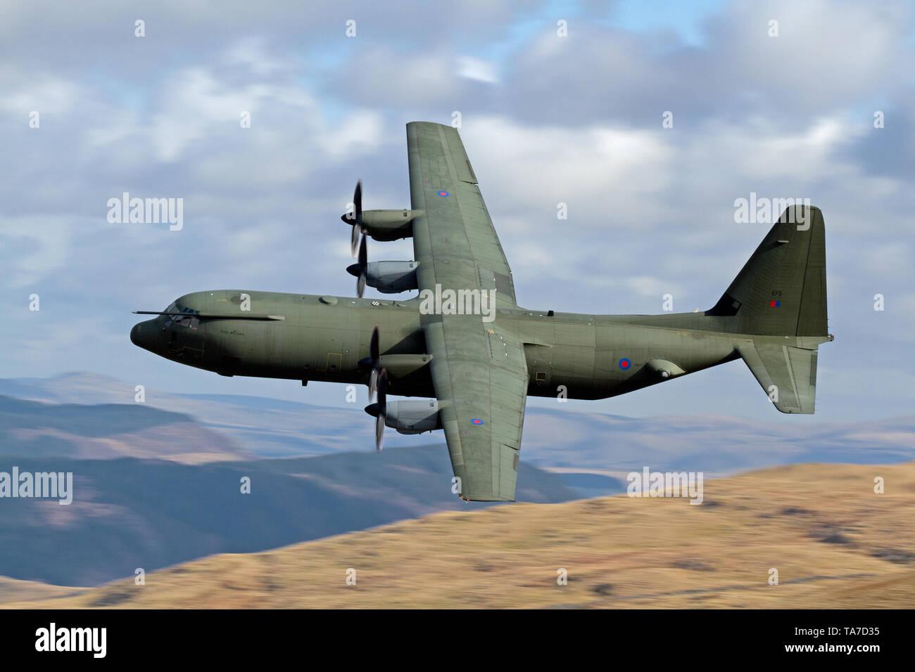 RAF Lockheed C-130 Hercules flying low level in the Mach Loop in Wales, UK Stock Photo