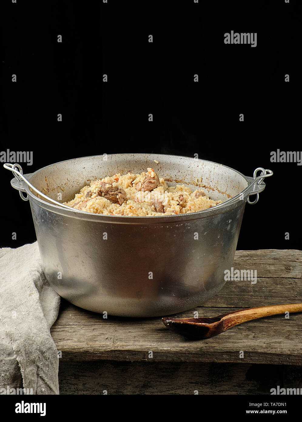 Pilaf is an oriental dish of boiled rice with fat and slices of meat and spices. the dish is cooked in a large aluminum cauldron, black background - Stock Image