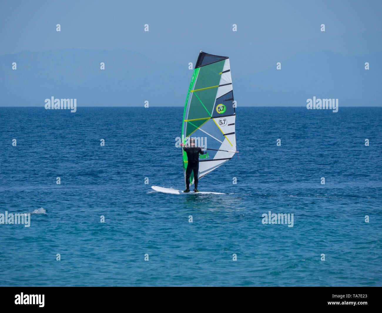 anonymous person with wind surfing in clear open sea ocean - Stock Image