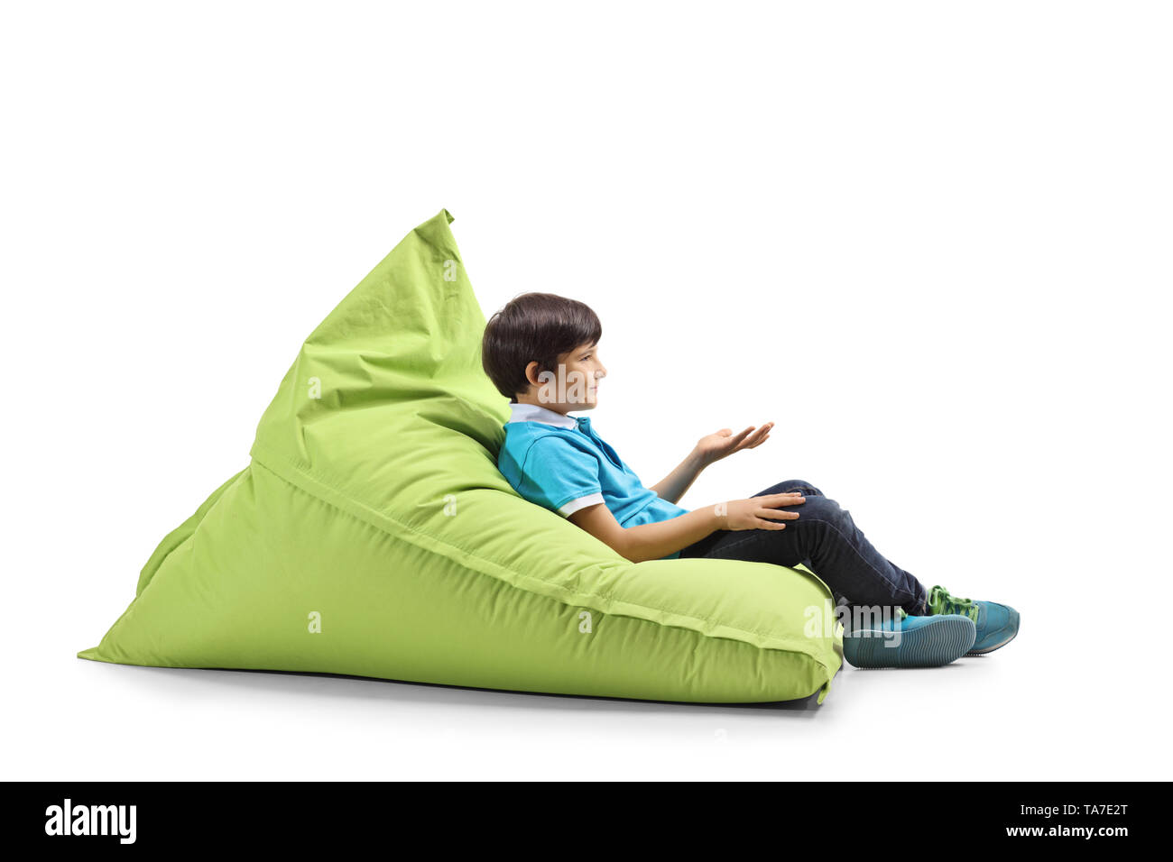 Full length profile shot of a boy sitting on a green bean bag and gesturing with hand isolated on white background - Stock Image