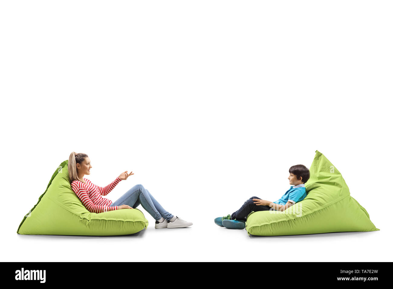 Full length profile shot of a young woman and a male child sitting on bean bags having a conversation isolated on white background - Stock Image