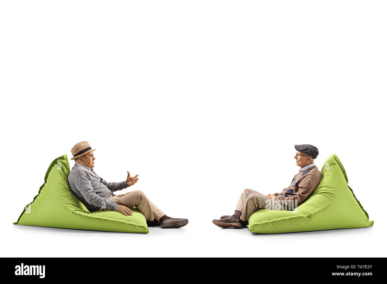 Full length profile shot of two seniors talking and sitting on green bean bags isolated on white background - Stock Image