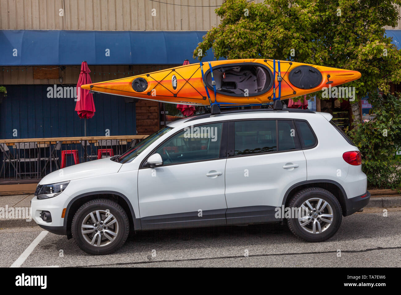 Sport Kayak mounted on the roof of a white vehicle on the Sunshine Coast of British Columbia Canada - Stock Image