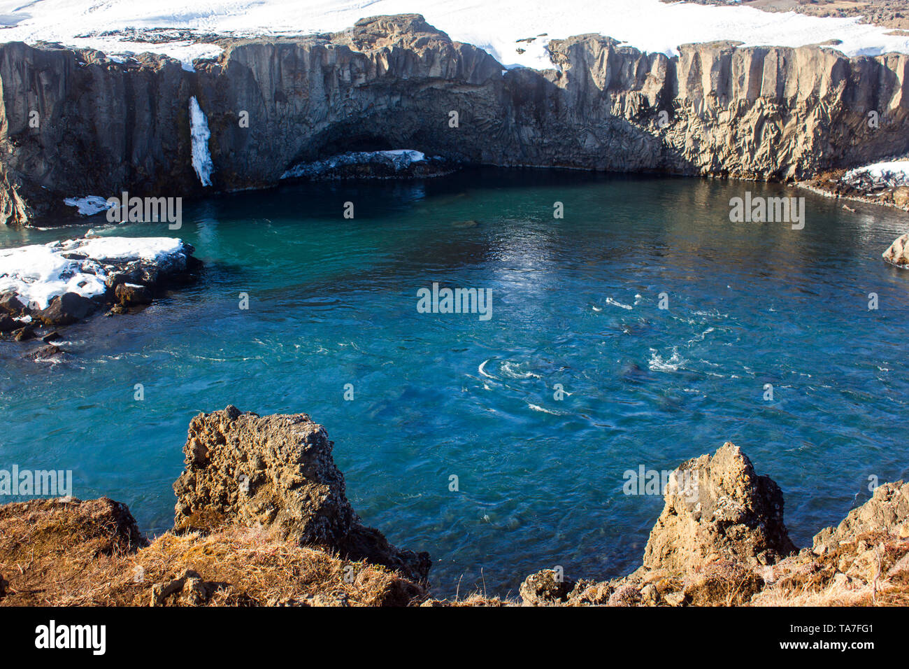 Columnar basalt formation over turquoise water with sunny weather in iceland - Stock Image