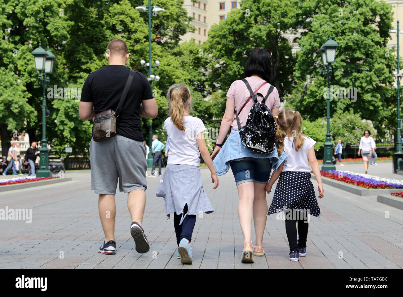 A family with kids walking in a city park, rear view. Couple with two daughters in summer, concept of parenthood, family leisure and travel - Stock Image
