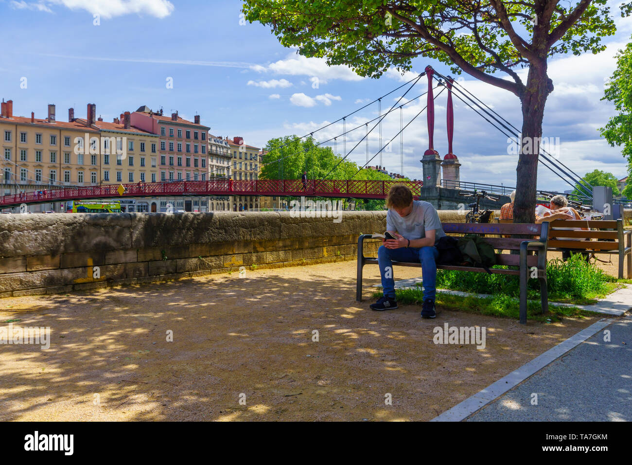 Lyon, France - May 10, 2019: The Saone River, and Saint-Gorges bridge, with locals and visitors, in Old Lyon, France - Stock Image