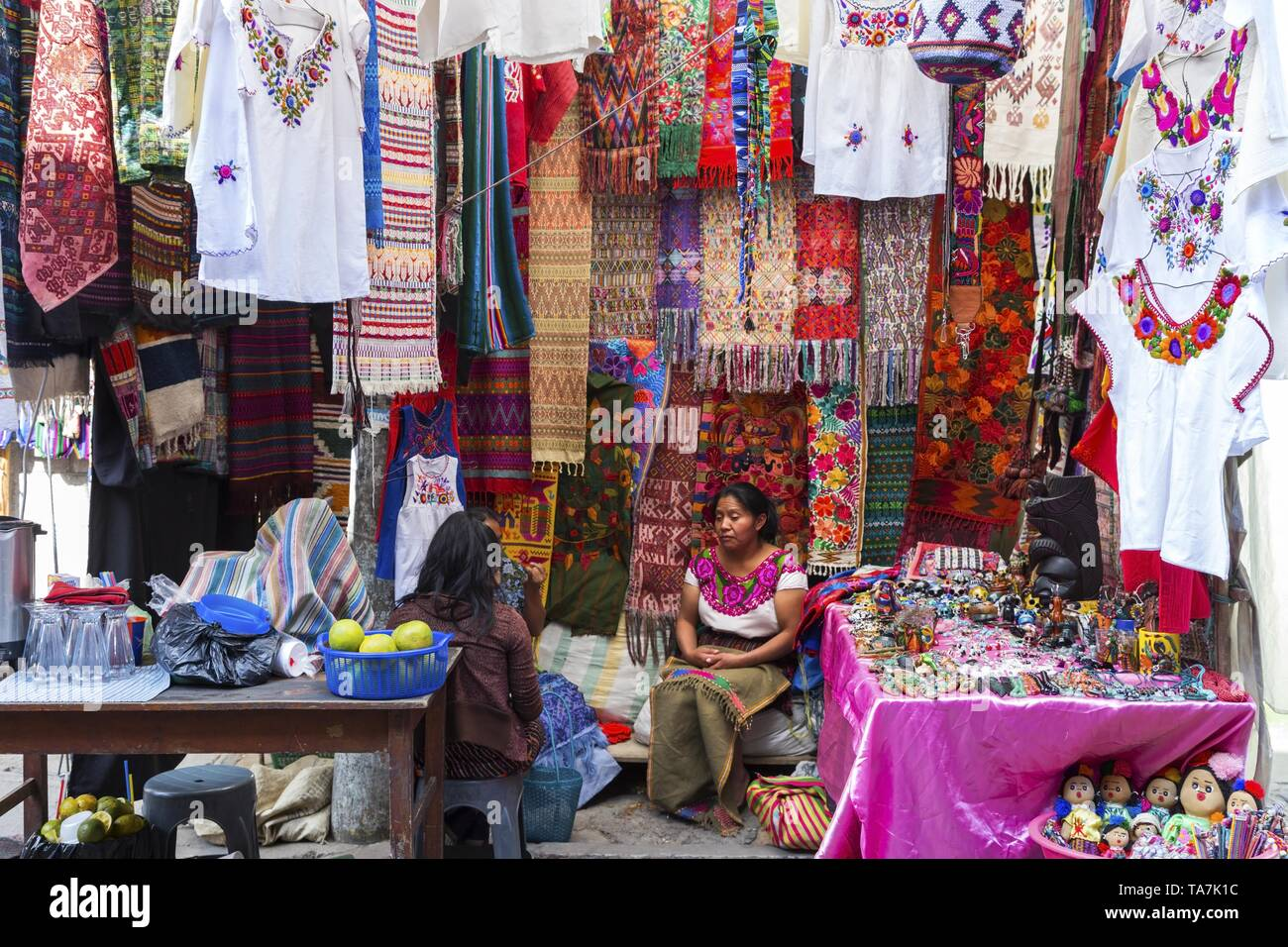 Ethnic People Sitting and Selling Traditional Textile, Carpets and Clothing on a Thursday Market Day in City of Chichicastenango or Chichi Guatemala Stock Photo