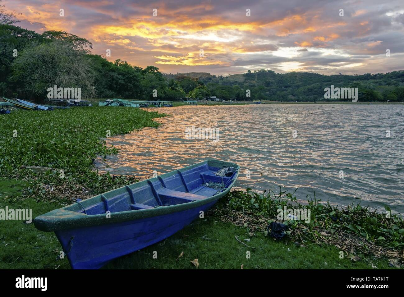 Blue Fishing Boat on Shore of Beautiful Lake Suchitlan and Dramatic Sunset Sky near Town of Suchitoto in El Salvador Stock Photo
