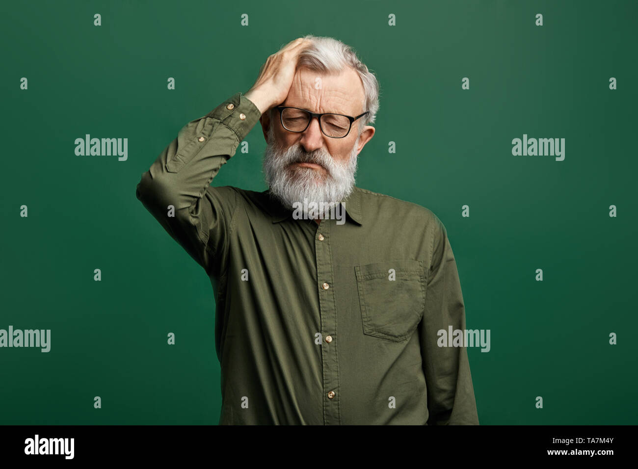 attractive old man in green T-shirt suffering from headache, intracranial pressure.close up portrait.tiredness, health problem,migraine. - Stock Image