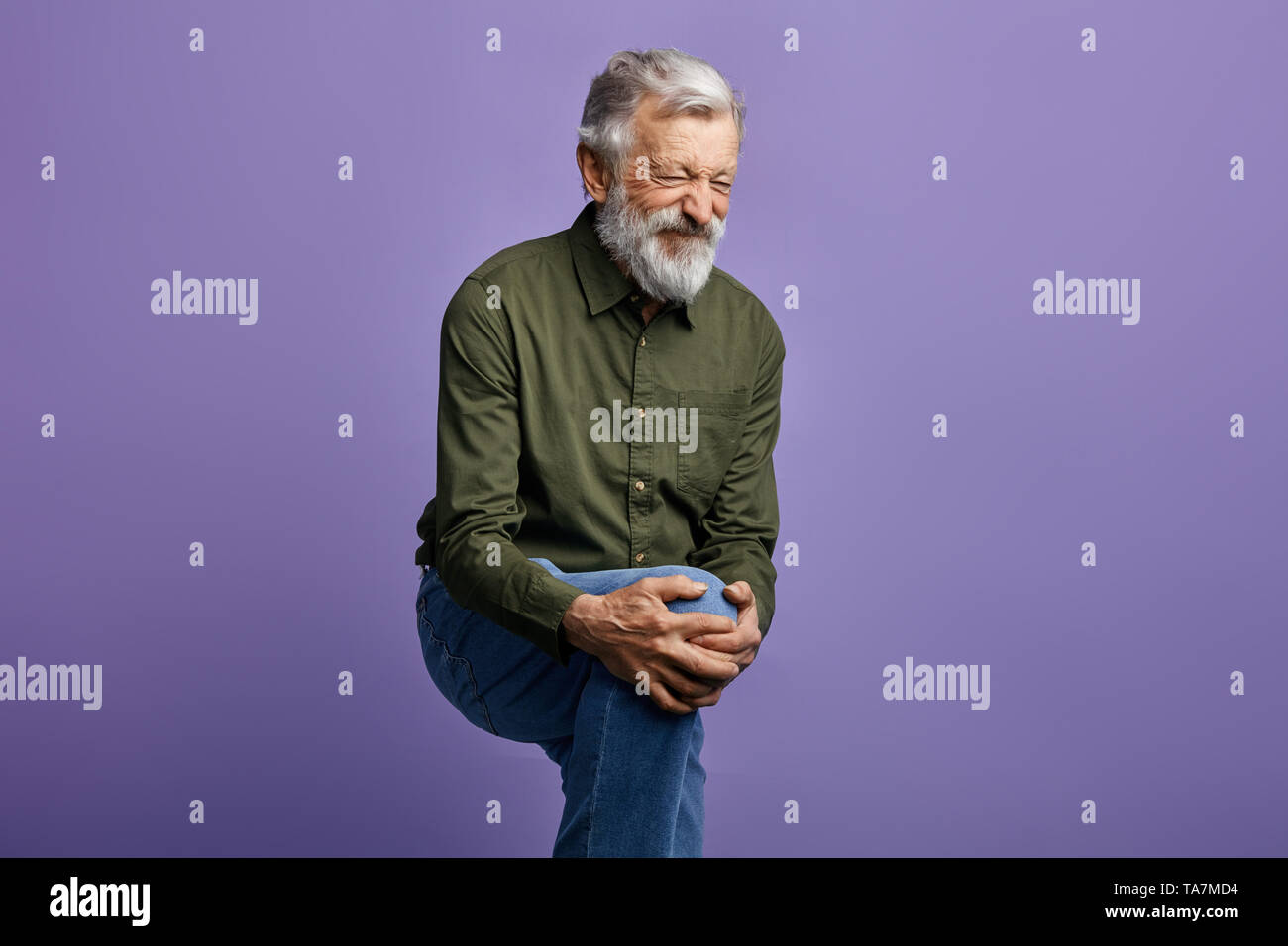 old man suffering from knee pain isolated on blue background. close up side view photo.health problems. man has bumped his knee. male has broken his l - Stock Image