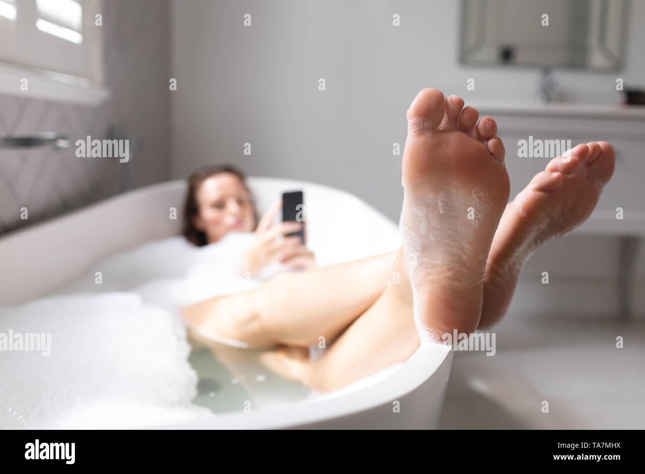 Woman lying in the bathtub with her legs crossed - Stock Image