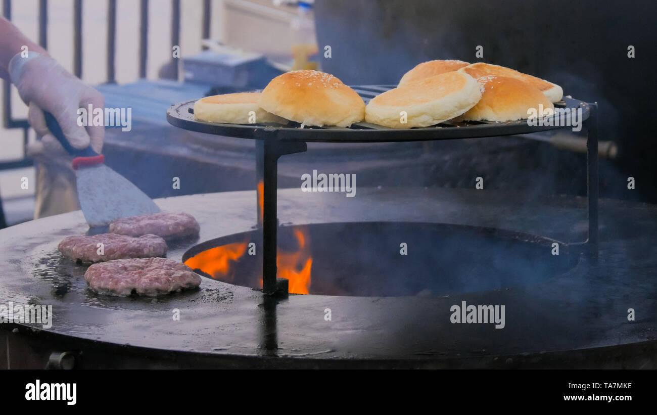 Chef preparing burgers at street food festival - Stock Image