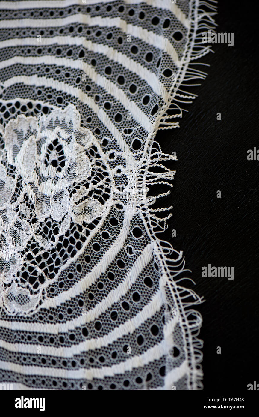 White lace on black background. The texture is close. - Stock Image