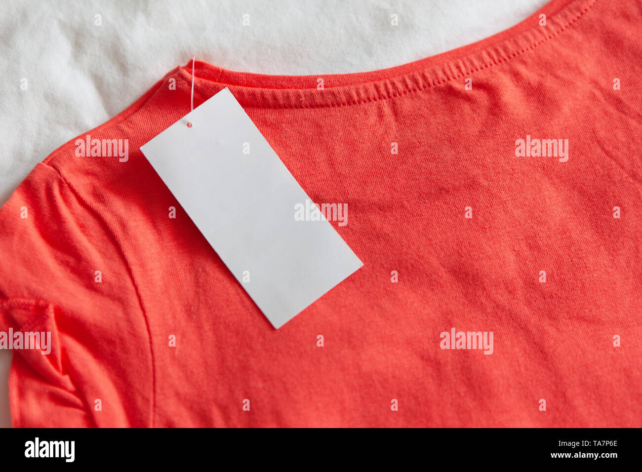 New pink red kid's or women's t-shirt with label on white background. Concept shopping, summer sales, discounts - Stock Image