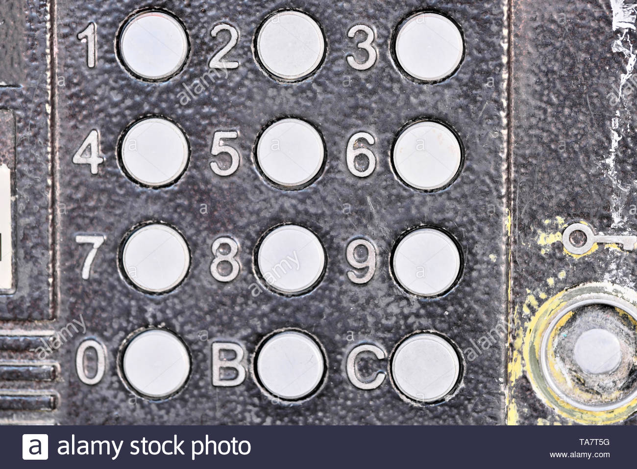 Panel doorphone dialing access code to open the entrance door of an urban apartment building close-up macro - Stock Image