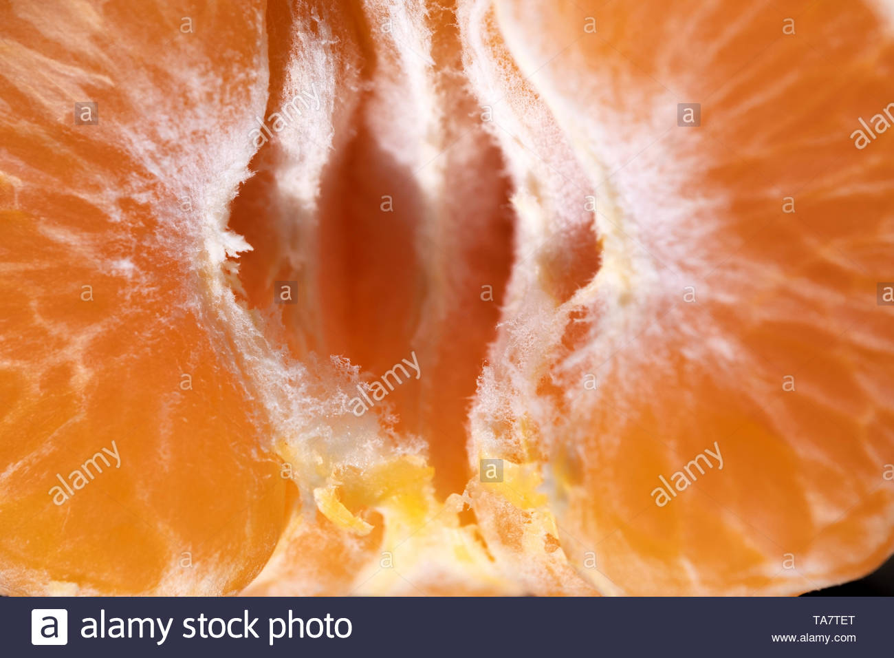 Peeled mandarin slices close-up shot from above, macro image - Stock Image