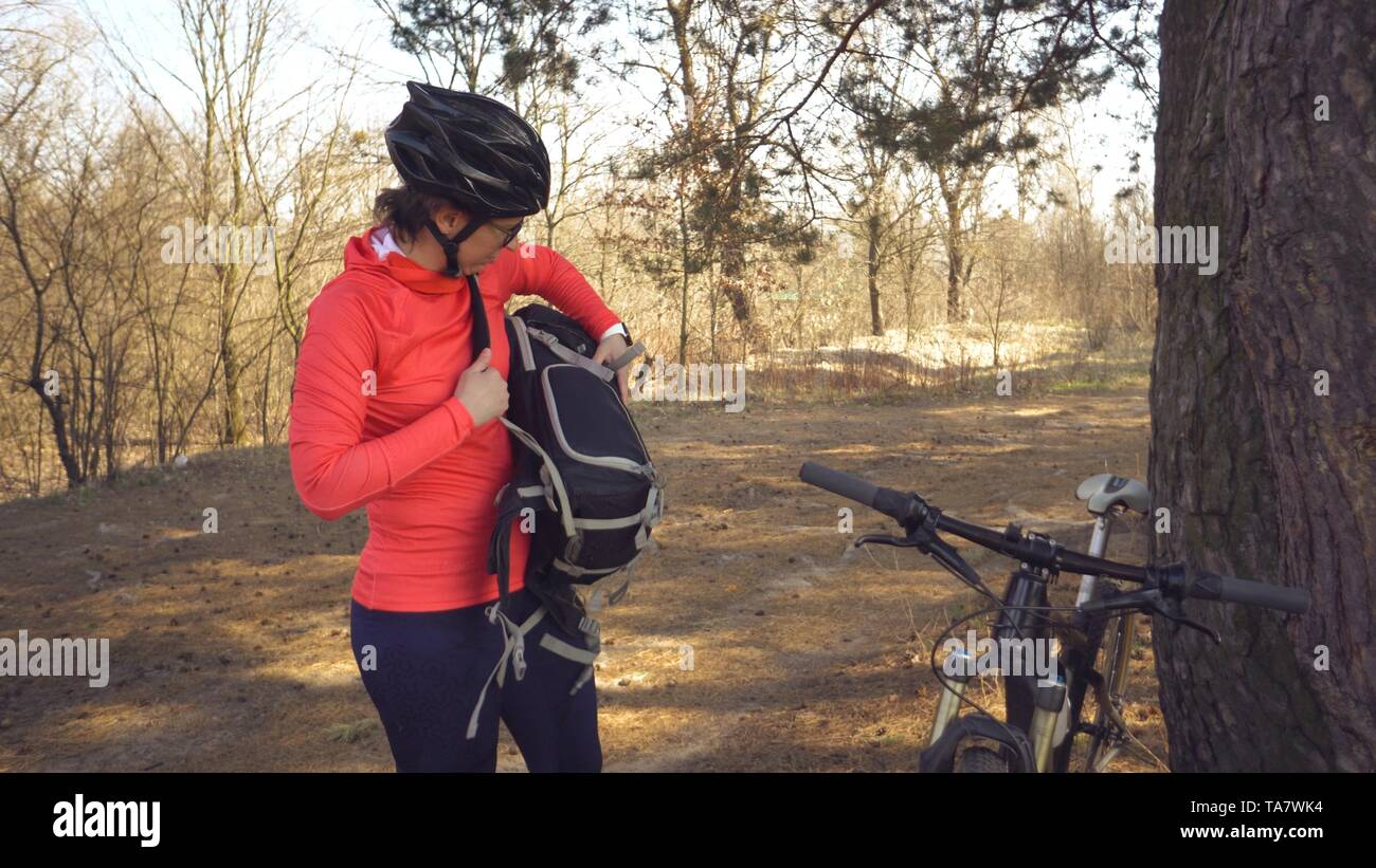 Caucasian Sport Cyclist Woman Sport Off Road Bike Park Near Tree A Female Athlete In Sportinvnoy Clothing And A Helmet And A Black Backpack Break Sto Stock Photo Alamy
