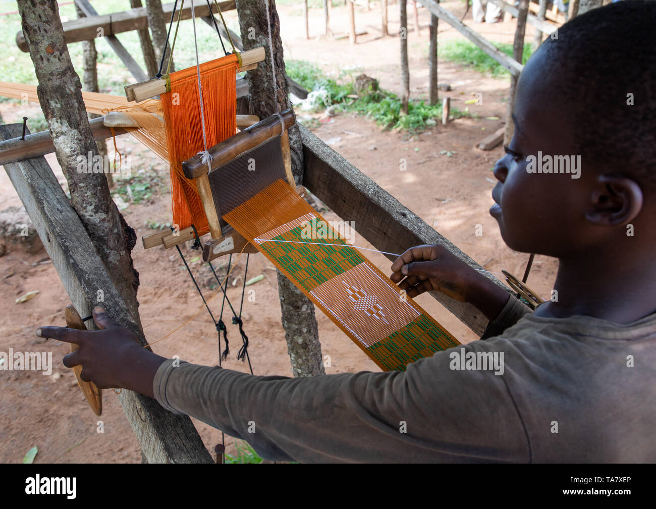 African man from Baoulé tribe weaving in a traditional textile factory, Région des Lacs, Bomizanbo, Ivory Coast - Stock Image