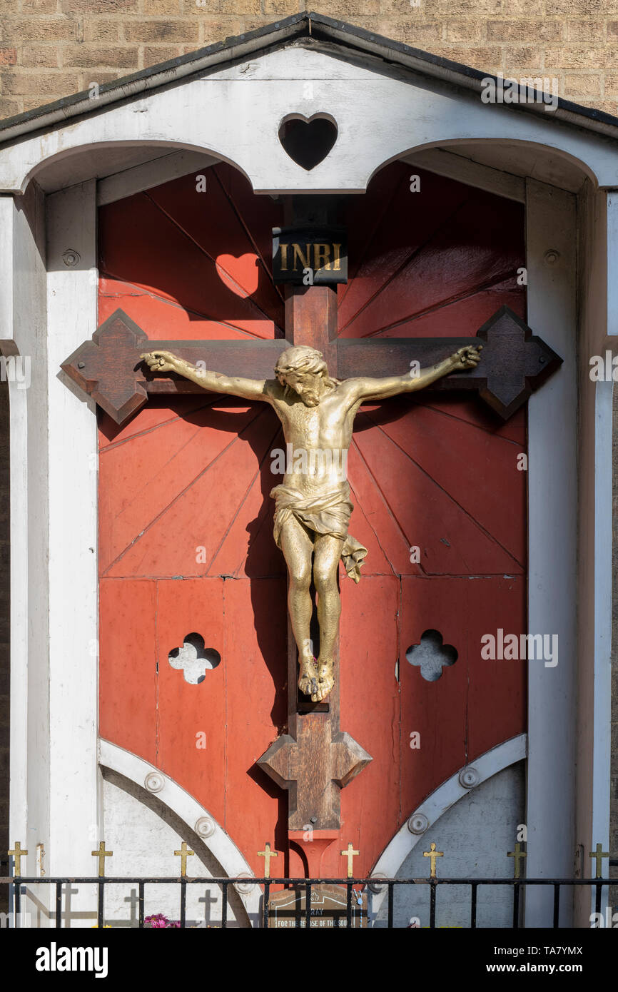 Statue of Jesus christ crucifixion on the side of the Roman Catholic church Our Lady of Mount Carmel and St Simon Stock in Kensington, London Stock Photo