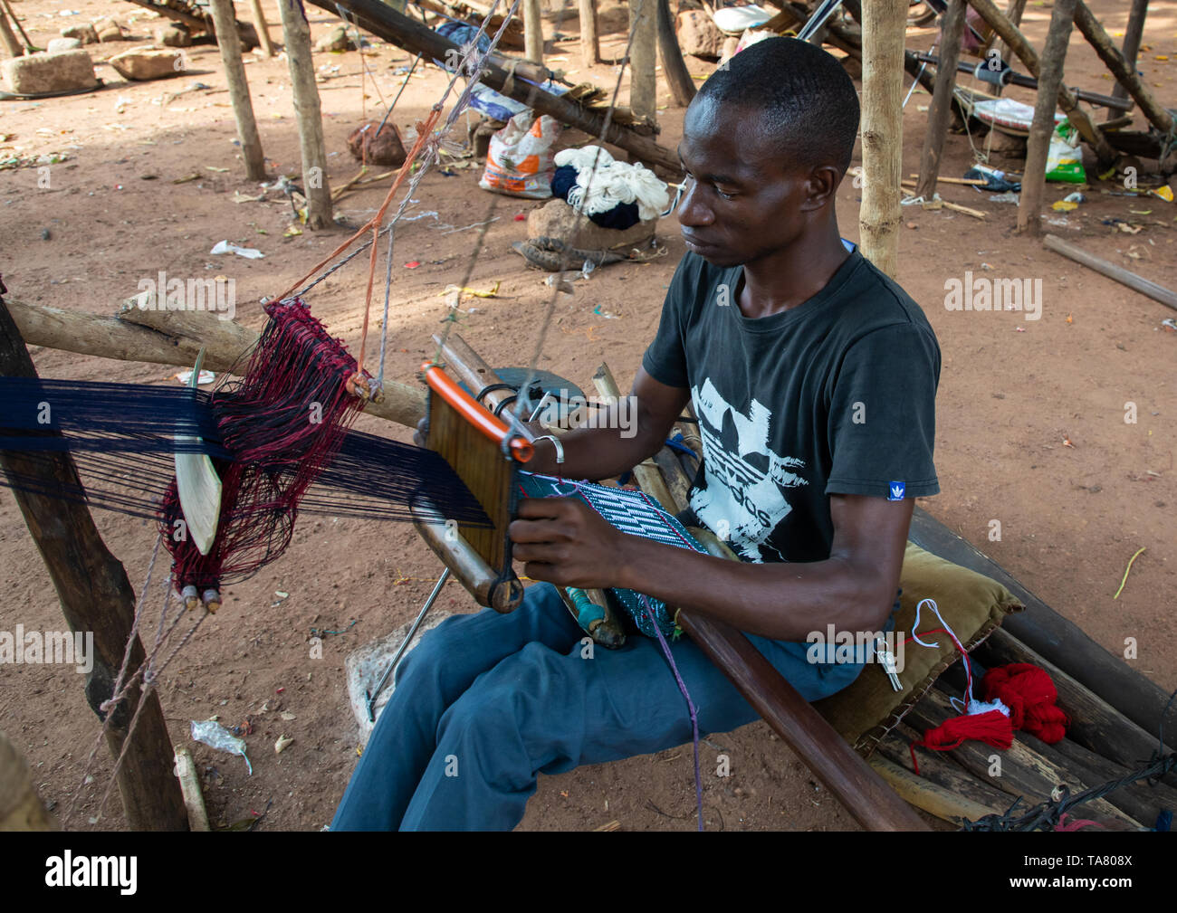 African man from Senufo tribe weaving in a traditional textile factory, Savanes district, Waraniene, Ivory Coast - Stock Image