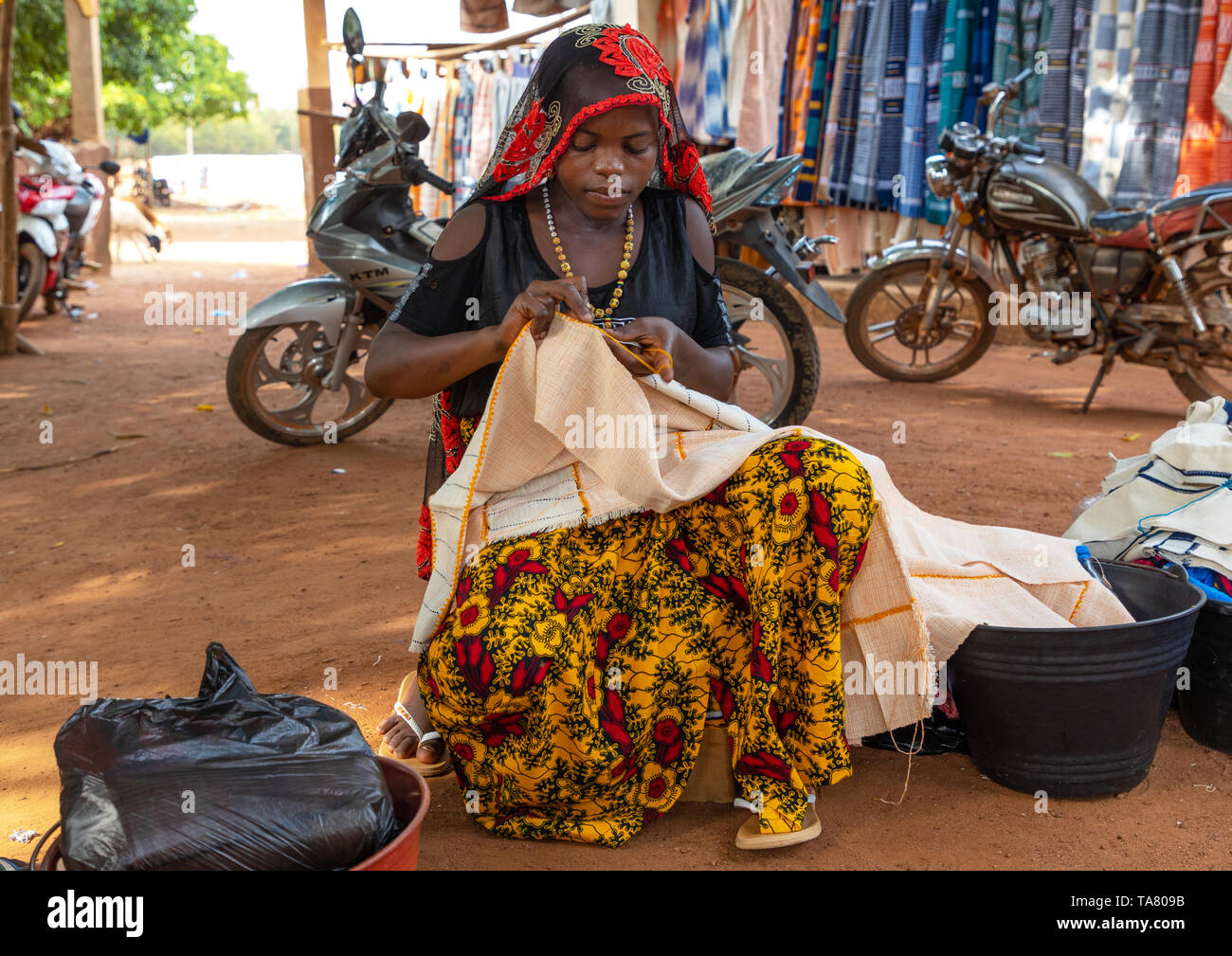 Senufo woman sewing in a market, Savanes district, Waraniene, Ivory Coast - Stock Image