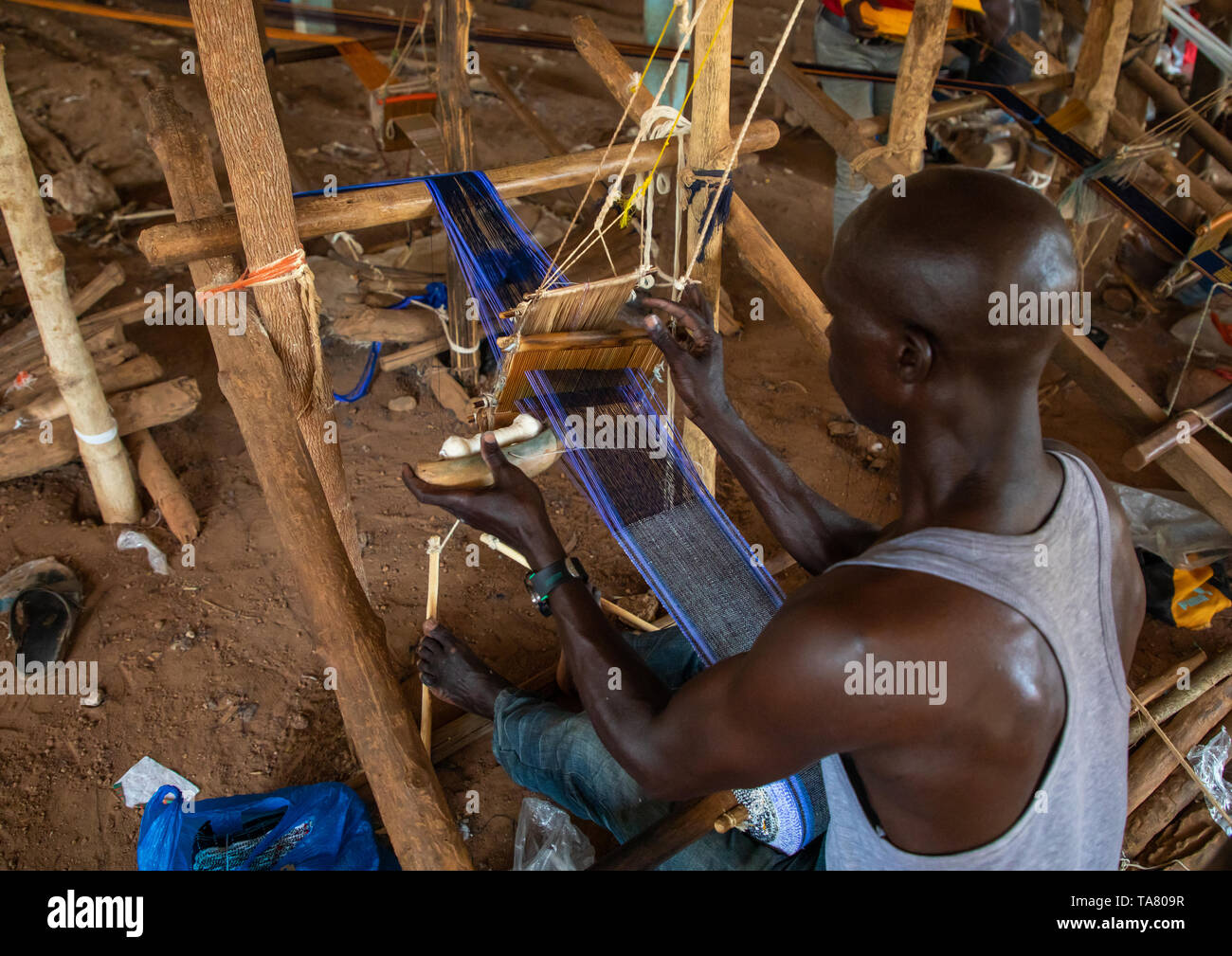 African man weaving in a traditional textile factory, Savanes district, Waraniene, Ivory Coast - Stock Image