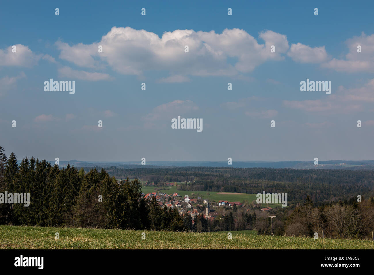 Little village in the middle of the german countryside with hills, forests, fields and meadows - Stock Image