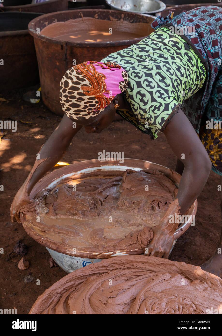Senufo woman prepairing shea butter in a traditional karité factory, Savanes district, Tcheregnimin, Ivory Coast Stock Photo