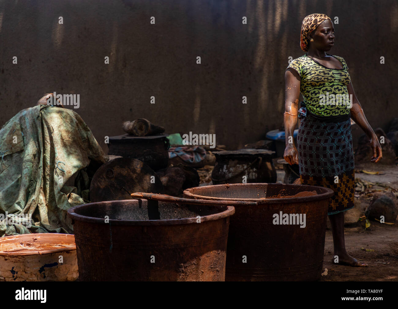 Senufo woman prepairing shea butter in a traditional karité factory, Savanes district, Tcheregnimin, Ivory Coast Stock Photo