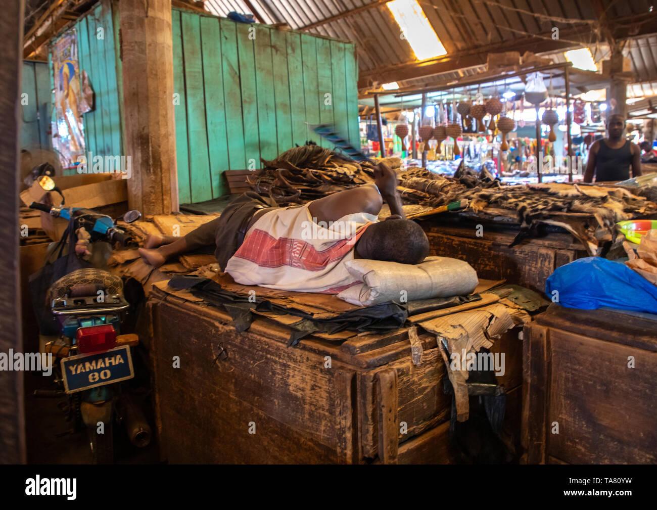 African man sleeping on a market stall during Ramadan, Poro region, Korhogo, Ivory Coast - Stock Image