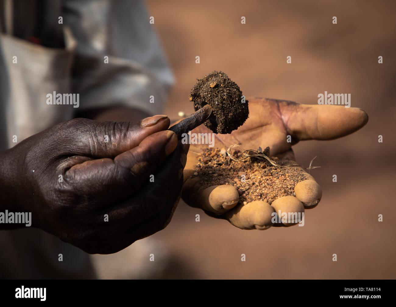 Senufo blacksmith using a magnet to find the metal, Poro region, Koni, Ivory Coast Stock Photo