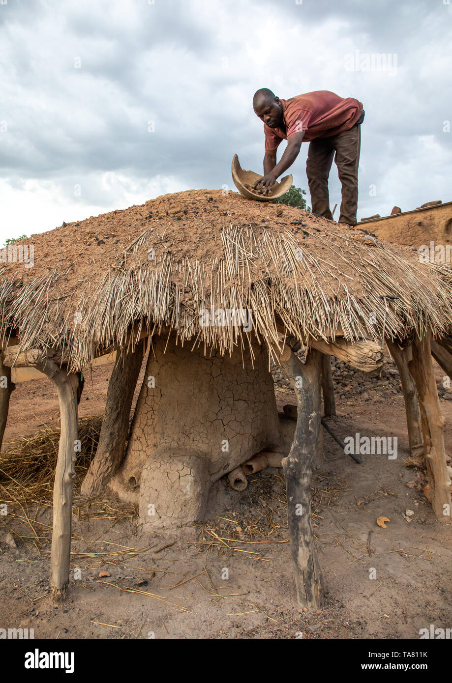 Senufo blacksmith putting charcoal from the top of the house, Poro region, Koni, Ivory Coast Stock Photo