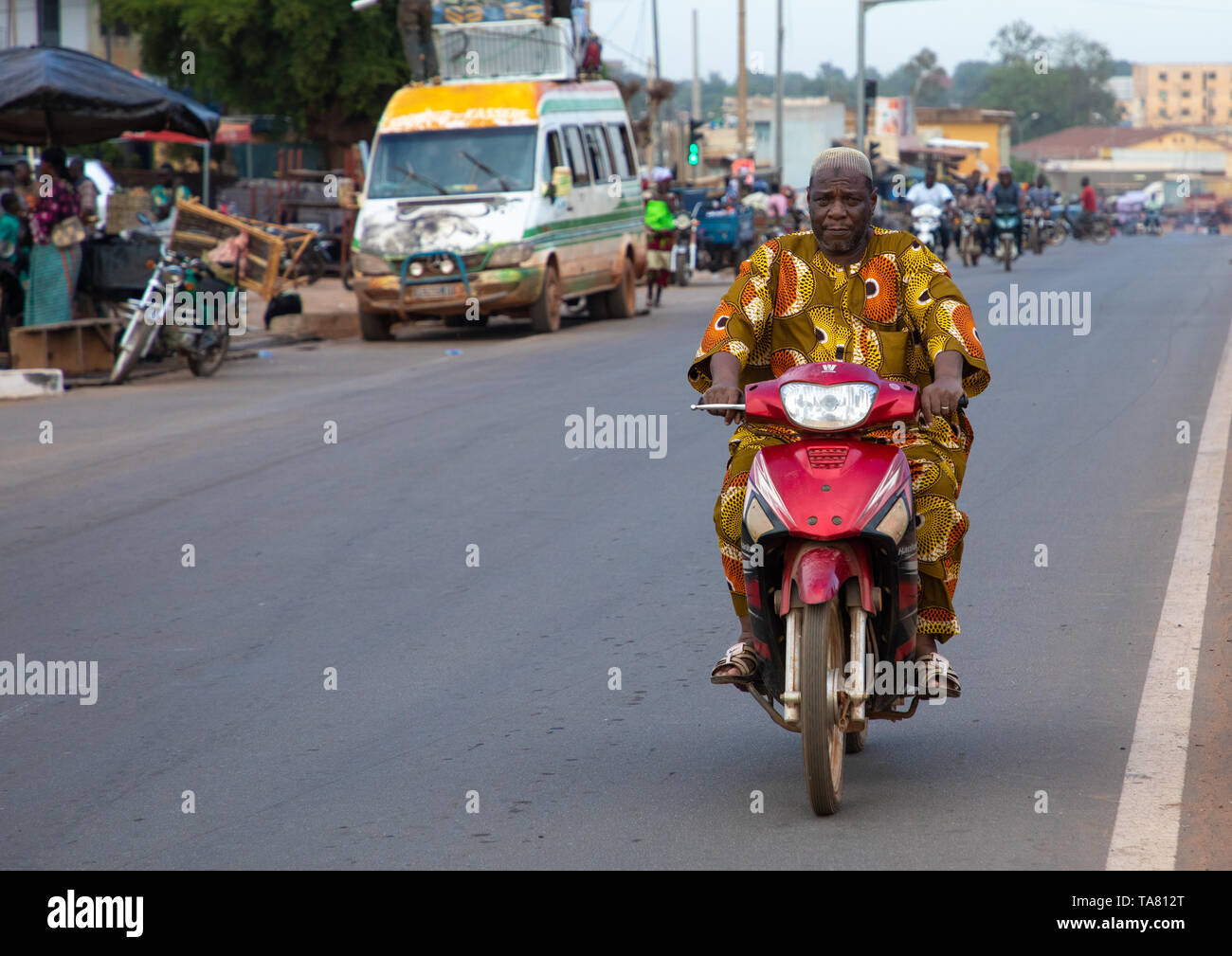 African man riding a motorbike in the street, Poro region, Korhogo, Ivory Coast Stock Photo