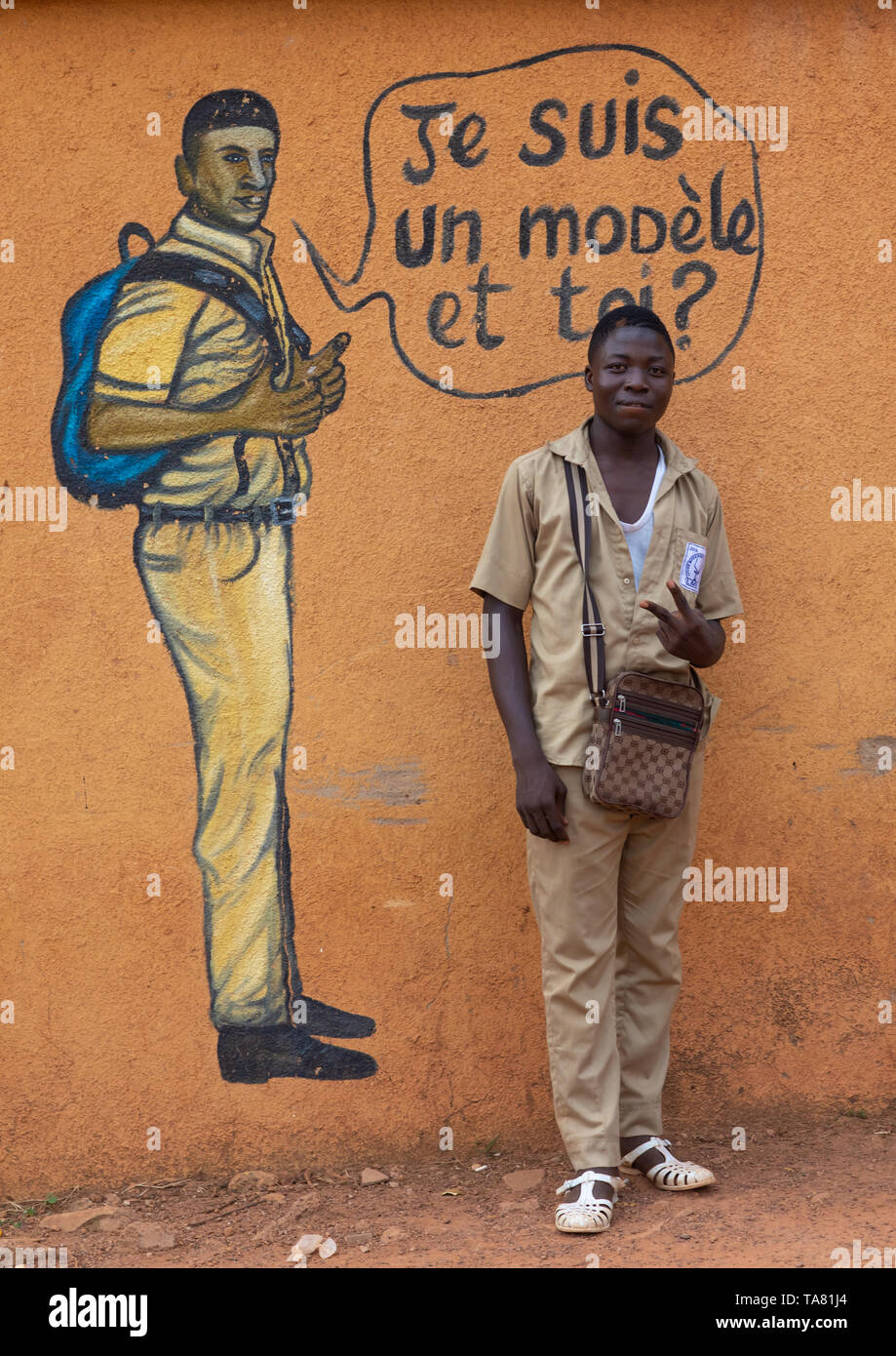 African boy standing in front of a mural depicting a pupil who works well at school, Savanes district, Boundiali, Ivory Coast Stock Photo