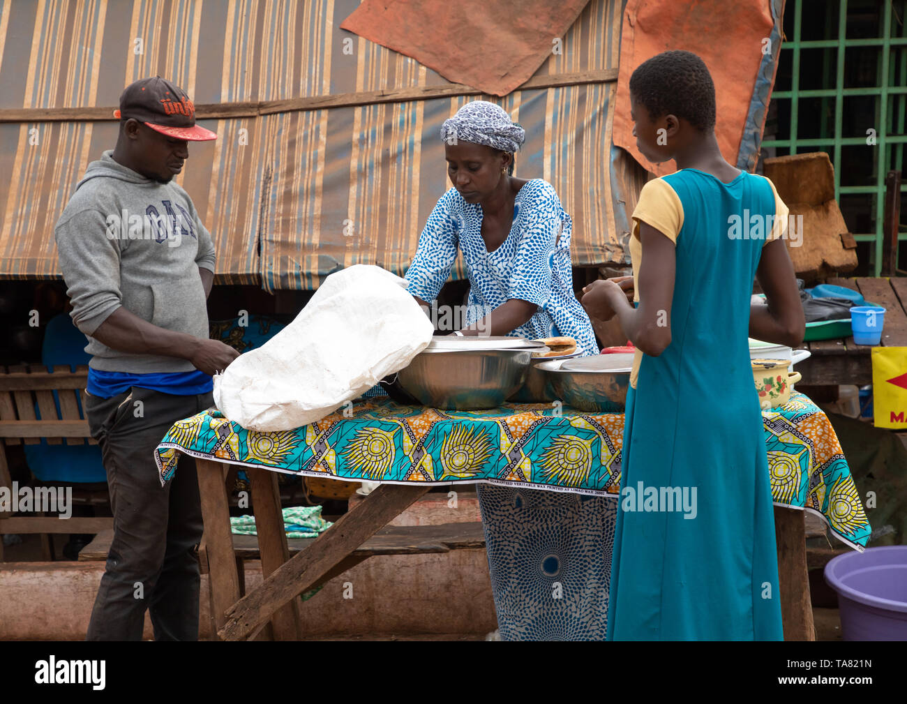 African woman sellling food in the sreet, Savanes district, Boundiali, Ivory Coast - Stock Image