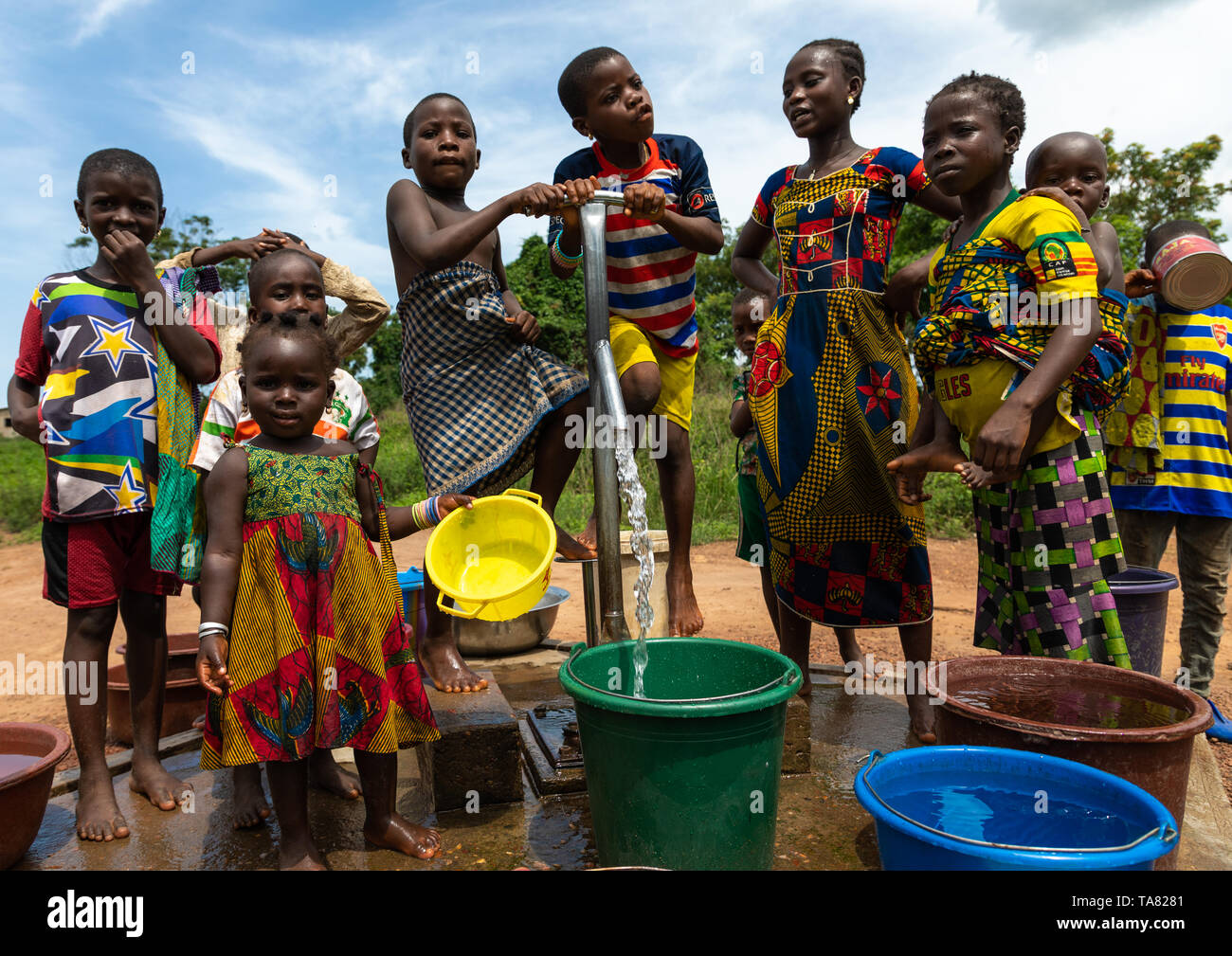 African children collecting water from a well with a pump, Bafing, Yo, Ivory Coast Stock Photo