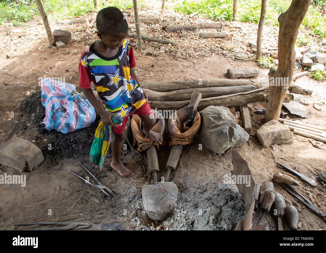 Child in a blacksmith workshop, Bafing, Yo, Ivory Coast Stock Photo