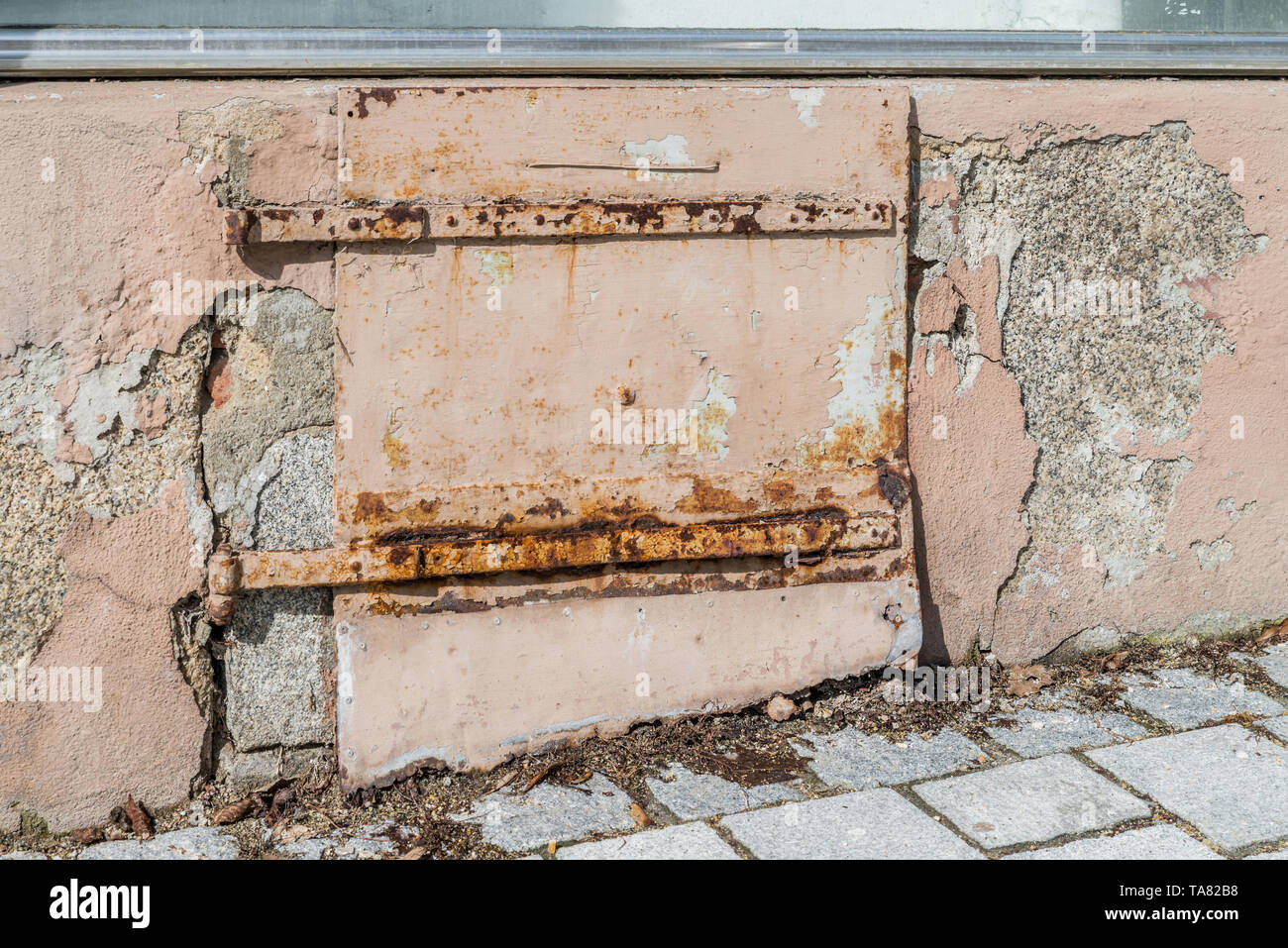 Old damaged rusty iron flap of a coal shaft at a house wall, Germany - Stock Image