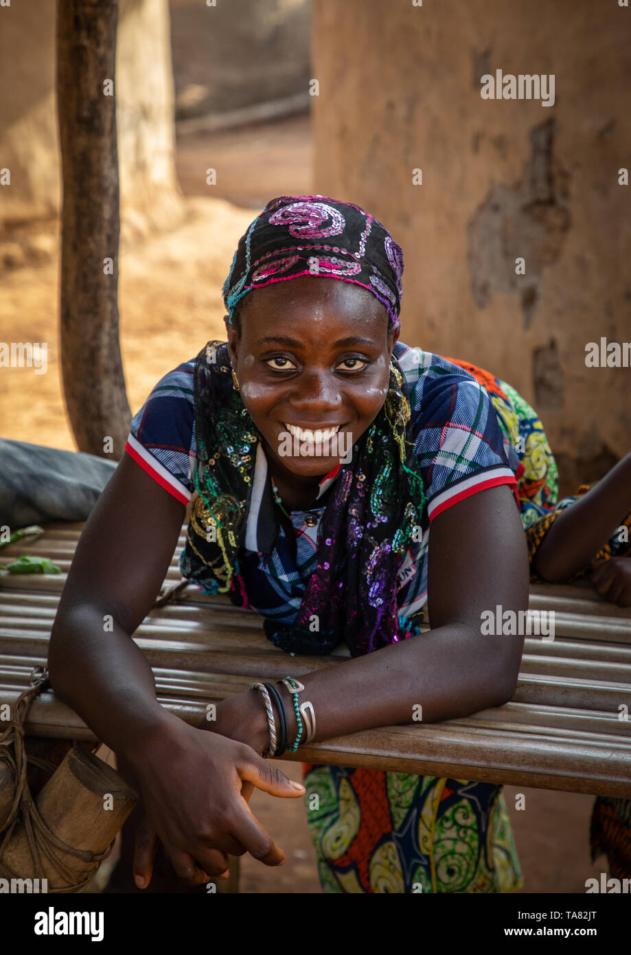 Portrait of a Dan tribe smiling woman resting on a wood bed, Bafing, Gboni, Ivory Coast Stock Photo