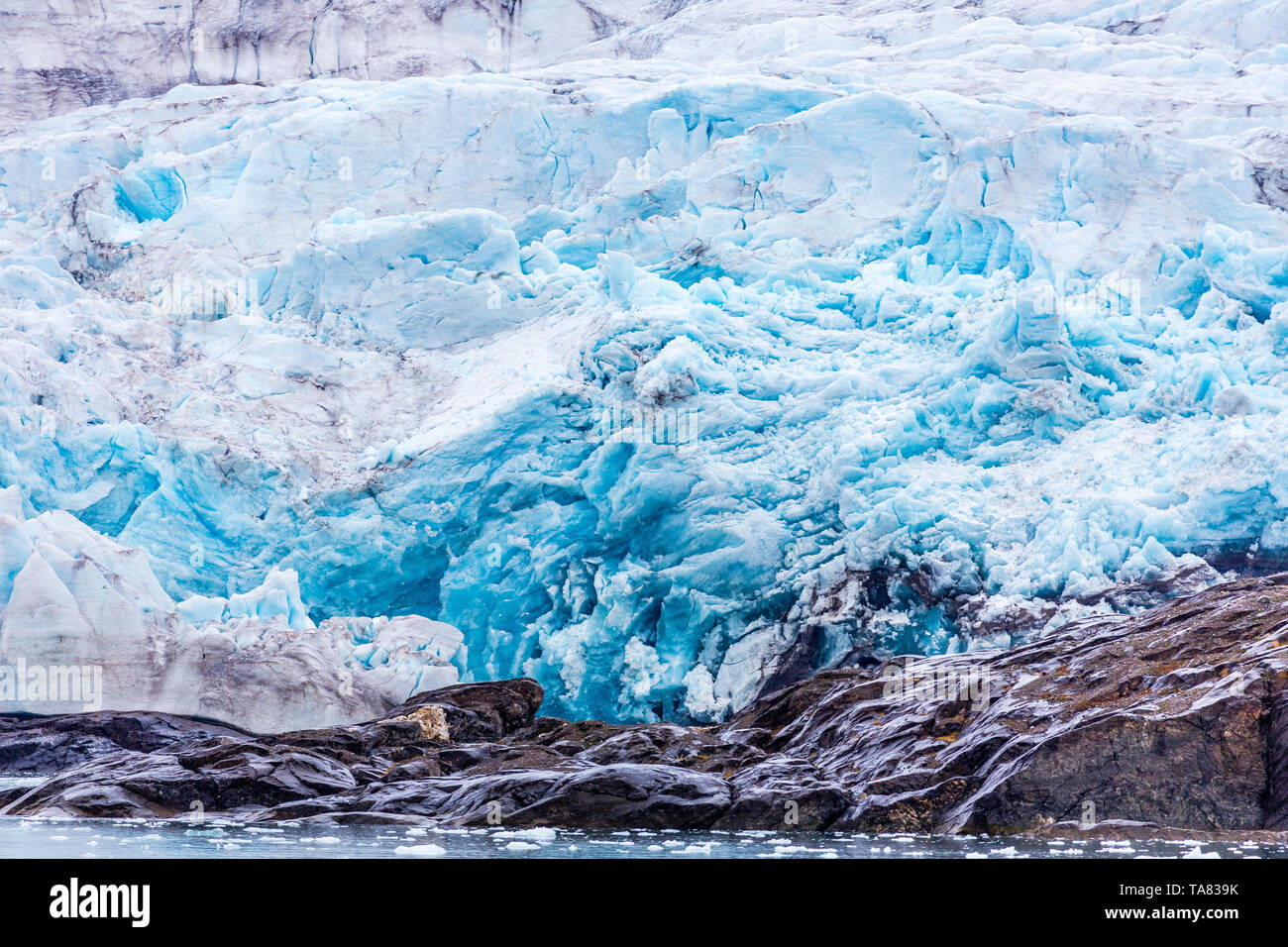At the edge of the blue shining glacier Nordenskiöldbreen near Pyramiden, on the coast of Billefjord, Svalbard. Norway - Stock Image