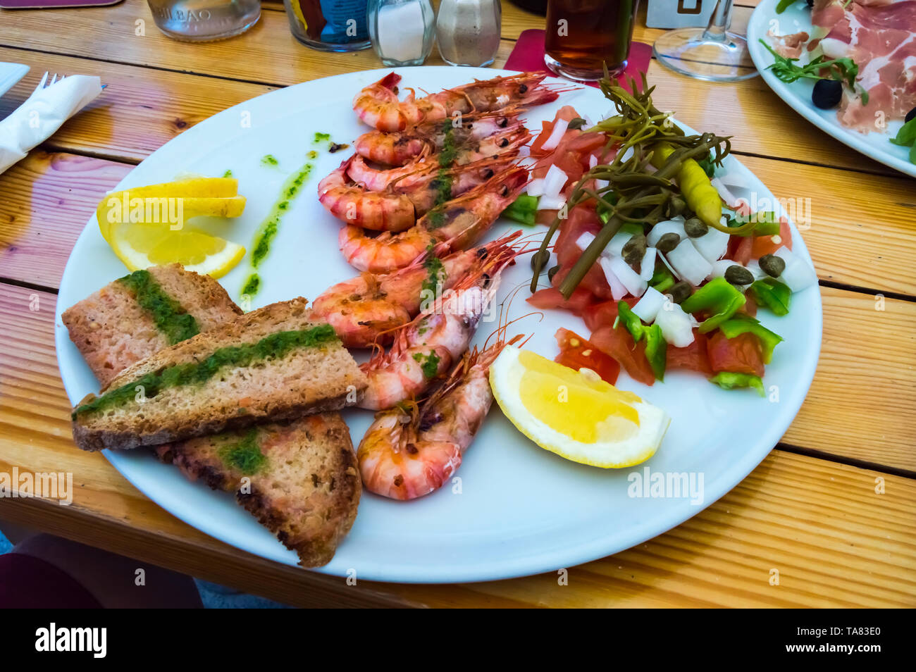 Plate of roasted prawns with slices of bread in the middle and tomatoes on a wooden table - Stock Image