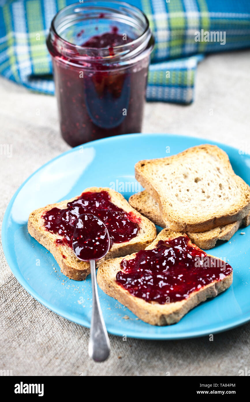 Toasted cereal bread slices on blue ceramic plate and homemade wild berries jam in jar, spoon and linen napkin closeup on rustic wooden table backgrou - Stock Image