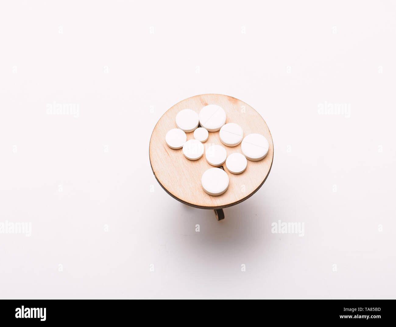 Medication regimen. Adherence to drug regimen. Tips tackling complex medication regimen. Take medicines after food. Health care and medical treatment. Vitamin supplements. Pills on tiny wooden table. - Stock Image